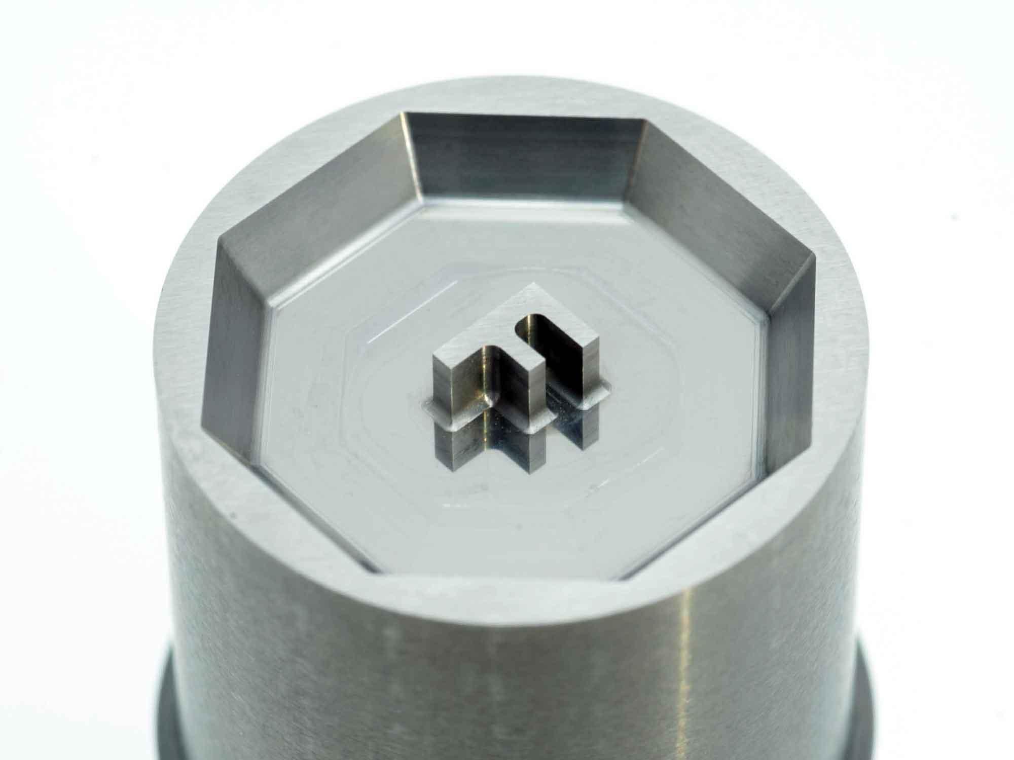 超硬金属に切削のみで斜め面を鏡面仕上げし「F」が映り込む様に加工